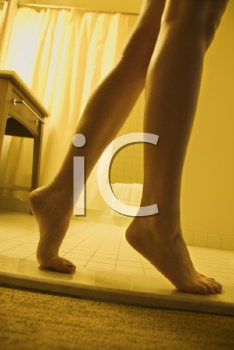 Bare legs and feet of woman standing on tiptoe in bathroom.