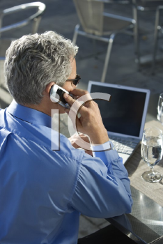 Royalty Free Photo of Businessman in a Suit Talking on a Cellphone and Looking at a Laptop