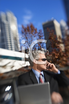 Royalty Free Photo of a Businessman in a Suit Sitting at a Patio Table Outside Talking on a Cellphone and Smiling