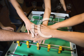 Royalty Free Photo of a Group of Friends Clasping Hands Over a Foosball Table