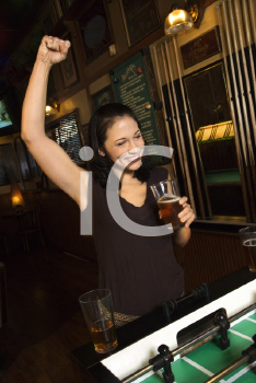 Royalty Free Photo of a Woman Smiling and Cheering on a Foosball Game