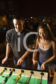 Royalty Free Photo of a Man and Woman Teamed Up at a Foosball Game in a Pub