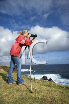 Royalty Free Photo of a Woman Holding a Camera on a Cliff Overlooking the Ocean in Maui, Hawaii