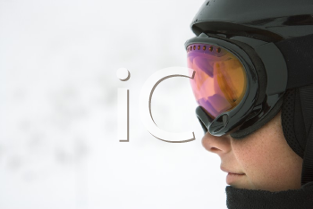 Royalty Free Photo of Profile of a Teenage Boy Skier Wearing a Helmet and Goggles at a Ski Resort on a Mountain