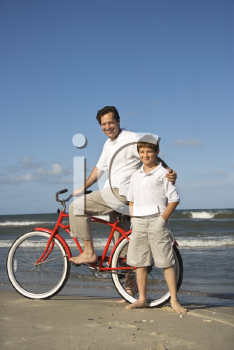 Royalty Free Photo of a Father Riding a Bike With His Son