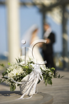 Royalty Free Photo of a Flower Basket With a Bride and Groom Blurred in the Background