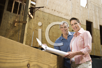 Royalty Free Photo of a Couple Holding Blueprints and Smiling