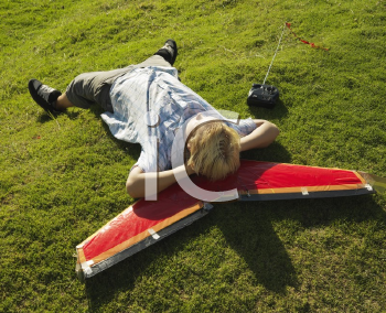 Royalty Free Photo of a Boy Laying and Resting His Head on an Airplane