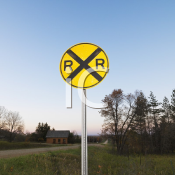 Royalty Free Photo of a Circular Yellow Railroad Grade Crossing Sign in Rural Setting