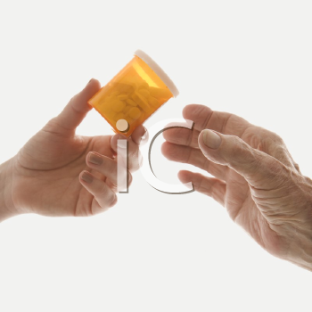 Royalty Free Photo of a Close-Up of a Caucasian Female's Hand Handing a Medication Mottle to an Elderly Caucasian Male Hand