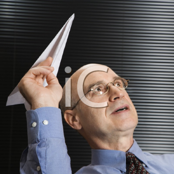 Royalty Free Photo of a Businessman Playing With a Paper Airplane