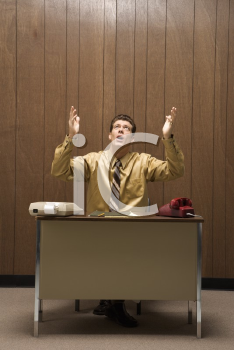 Royalty Free Photo of a Businessman Sitting at a Desk Raising Hands in the Air With a Look of Frustration
