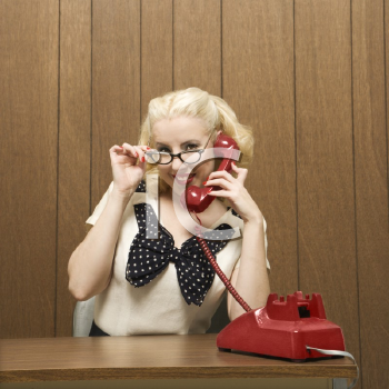 Royalty Free Photo of a Female Dressed in a Retro Outfit Holding a Red Phone Receiver