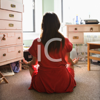 Royalty Free Photo of a Back View of a Woman in a Red Robe Sitting on the Floor Meditating in Lotus Pose