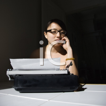 Young Asian woman sitting at kitchen table with typewriter.