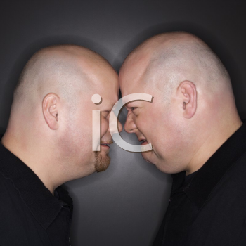 Royalty Free Photo of Identical Twin Men Standing Face to Face With Angry Expressions