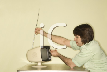 Royalty Free Photo of a Man Sitting at a 50's Retro Dinette Set Tapping an Old Television Set