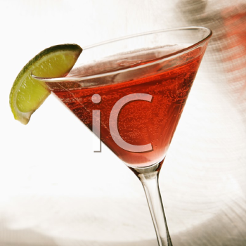 Still life of martini mixed drink with raspberry fruit agaisnt white background.