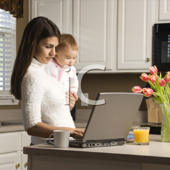 Royalty Free Photo of a Mother Holding Her Baby and Typing on a Laptop in the Kitchen