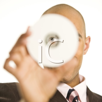 Royalty Free Photo of a Man Holding a CD Over His Face