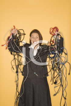 Royalty Free Photo of a Businesswoman Smiling Holding a Pile of Tangled Cords and Wires