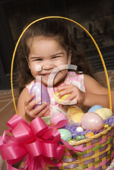 Hispanic girl holding egg from Easter basket looking at viewer smiling.