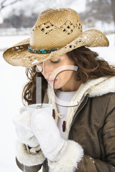 Royalty Free Photo of a Woman Holding a Coffee Cup and Wearing a Cowboy Hat