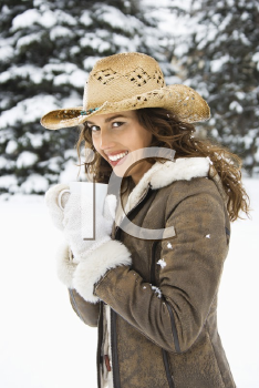 Royalty Free Photo of a Woman Wearing a Straw Cowboy Hat Outdoors in the Snow Holding a Coffee Cup