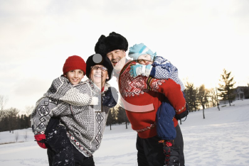Royalty Free Photo of Parents Carrying Their Son and Daughter Piggyback Style Smiling