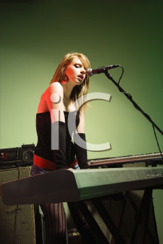 Royalty Free Photo of a Woman Singing into a Microphone and Playing Keyboard