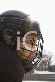 Royalty Free Photo of a Hockey Player Boy in a Cage Helmet With a Look of Concentration