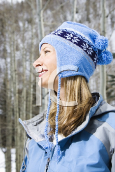 Royalty Free Photo of a Profile of a Smiling Blond Woman Wearing a Blue Ski Cap