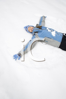 Royalty Free Photo of a Woman Lying in the Snow Making a Snow Angel