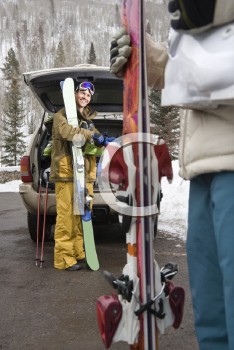 Royalty Free Photo of a Couple Standing by a Vehicle With Ski Equipment