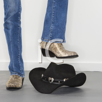 Royalty Free Photo of a Woman Wearing Snakeskin Cowboy Boots About to Stomp on a Black Cowboy Hat