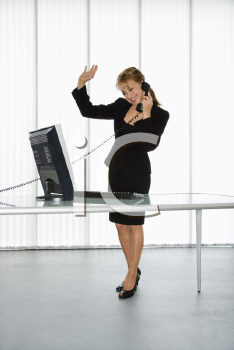 Royalty Free Photo of a Businesswoman Standing at the Computer Desk Waving While on the Telephone