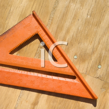 Royalty Free Photo of a Triangular Ruler on Unfinished Wood