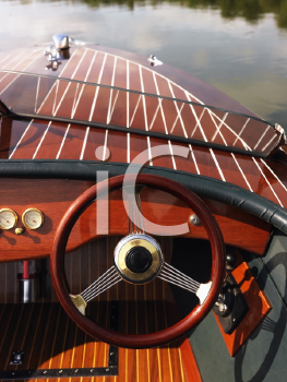Wooden boat with steering wheel and dashboard floating in gentle water.