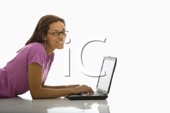 Royalty Free Photo of a Woman Lying on the Floor Using a Laptop and Smiling