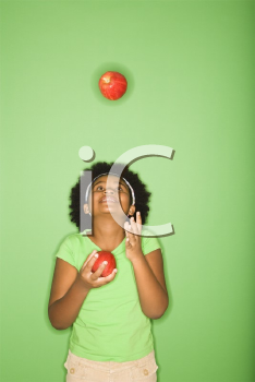 Royalty Free Photo of an African American Girl Juggling Apples