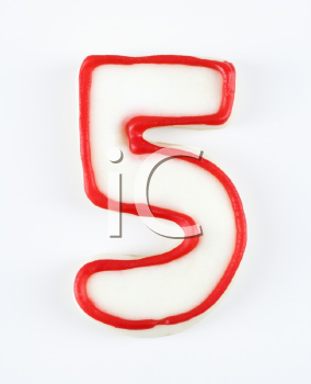 Sugar cookie in the shape of a number five outlined in red icing.