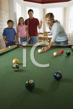 Woman playing pool with family in background. Vertically framed shot.