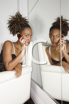 Attractive young woman using a cell phone while sitting in a white chair. She is being reflected in a mirror. Vertical shot.
