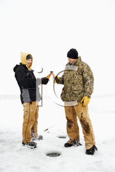 Two young men clink beers bottles while ice fishing. Vertical shot.