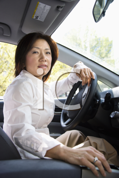 Asian woman driver sitting in car at steering wheel.