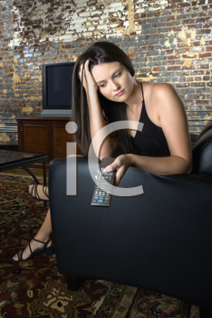 Pretty Caucasian young woman sitting in chair holding remote control looking bored.