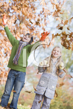 Royalty Free Photo of Two Children Playing in the Leaves