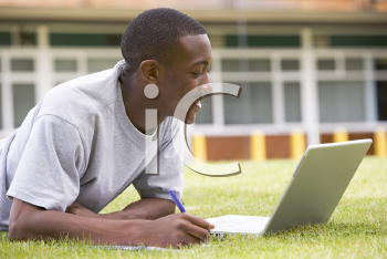 Royalty Free Photo of a Guy on the Lawn With a Laptop