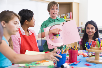 Royalty Free Photo of a Student Showing His Teacher and Classmates His Artwork