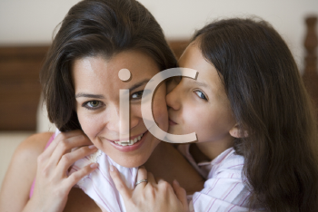 Royalty Free Photo of a Young Girl Kissing a Woman on the Cheek